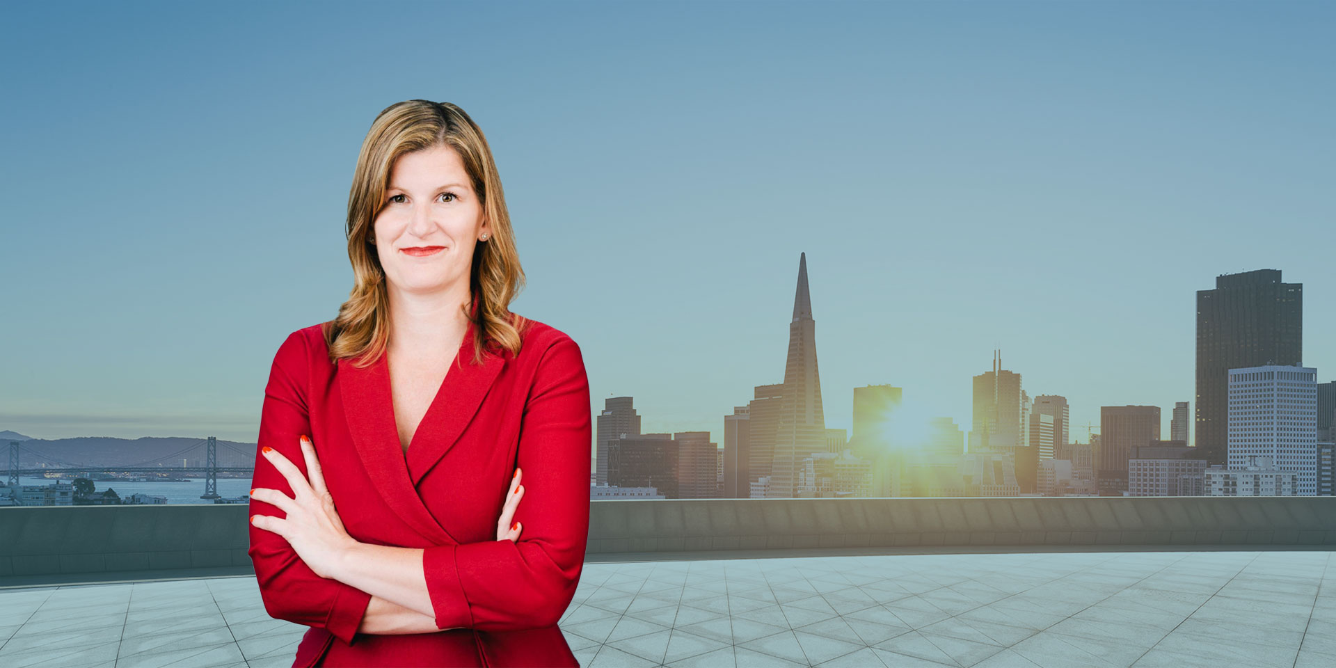 Sarah Nichols in a red suit with arms crossed standing on a roof with the San Francisco skyline in the background
