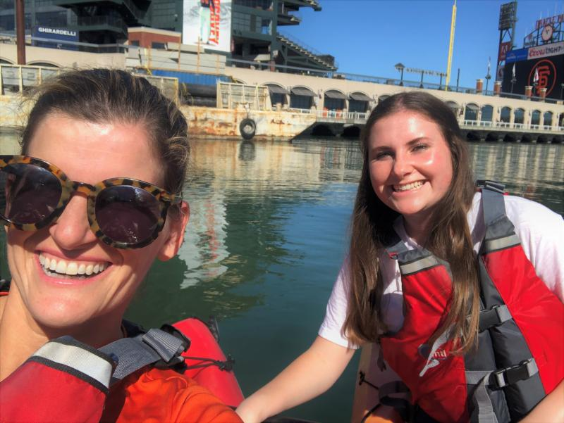 Attorney Sarah Nichols and Operations Manager Brooke Sutter wearing lifejackets in a kayak on the water