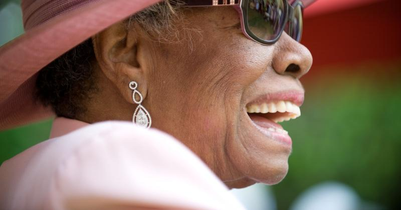 Sideview of Maya Angelou smiling wide, wearing sunglasses and a pink hat and jacket