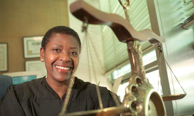 African American female judge smiling with scales of justice in front of her